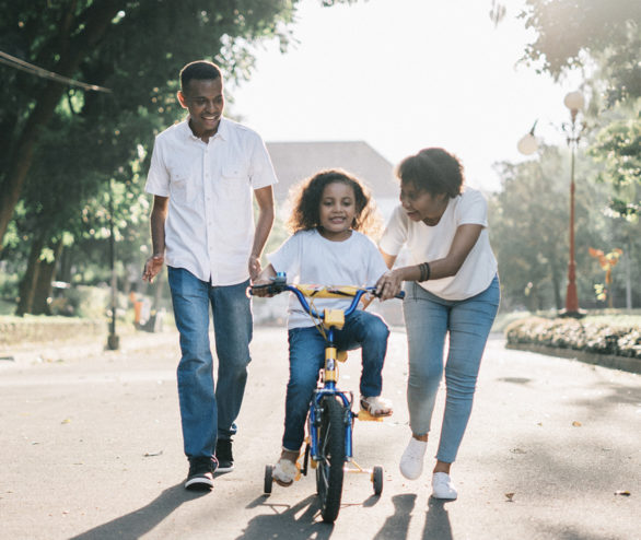 Family teaching child to ride a bike
